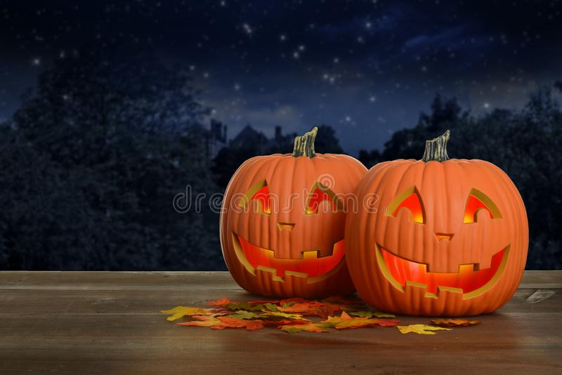 Two Halloween pumpkins at night glowing. On wood table with fall colored leaves stock photo