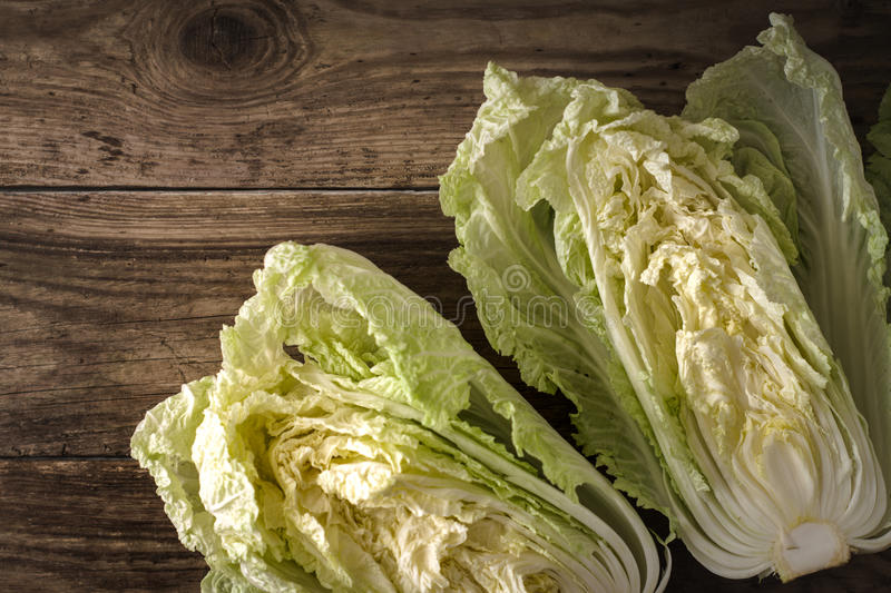 Two halves of chinese cabbage on old boards royalty free stock photos