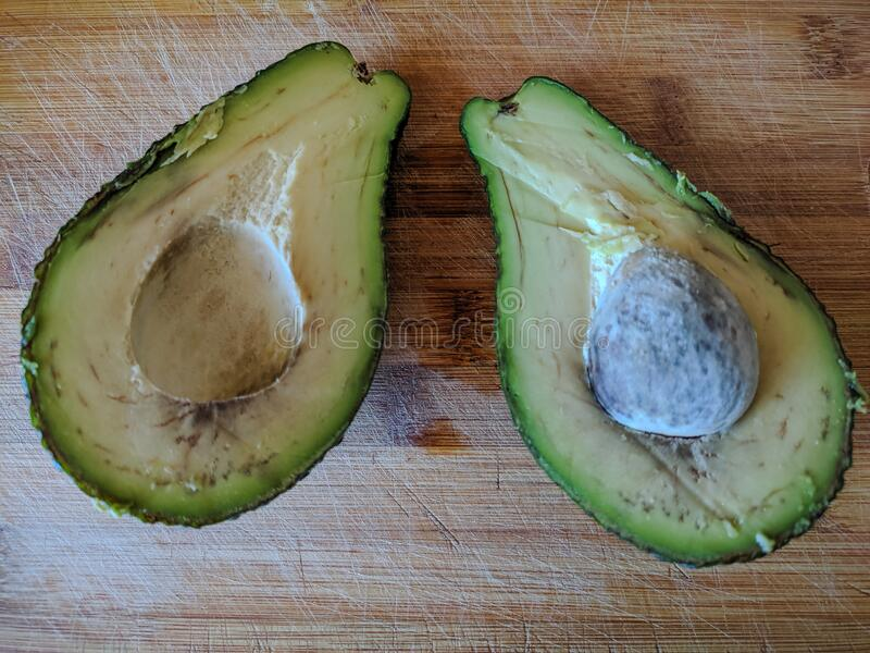 Two halves of green avocado with a bone on a wooden table. Close-up. Background stock images