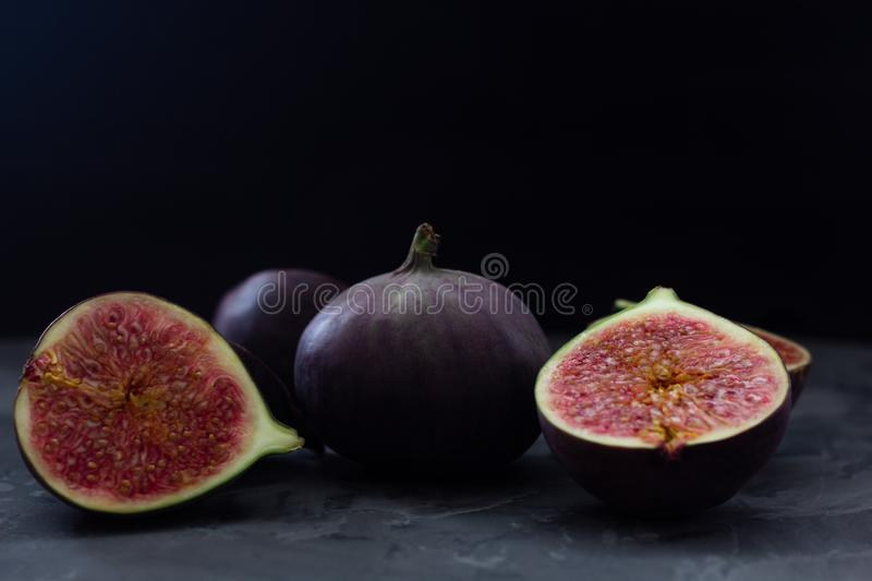 Two halves of juicy cut figs close-up on a background of fresh fruits. Dark background. low key. Copy space royalty free stock images