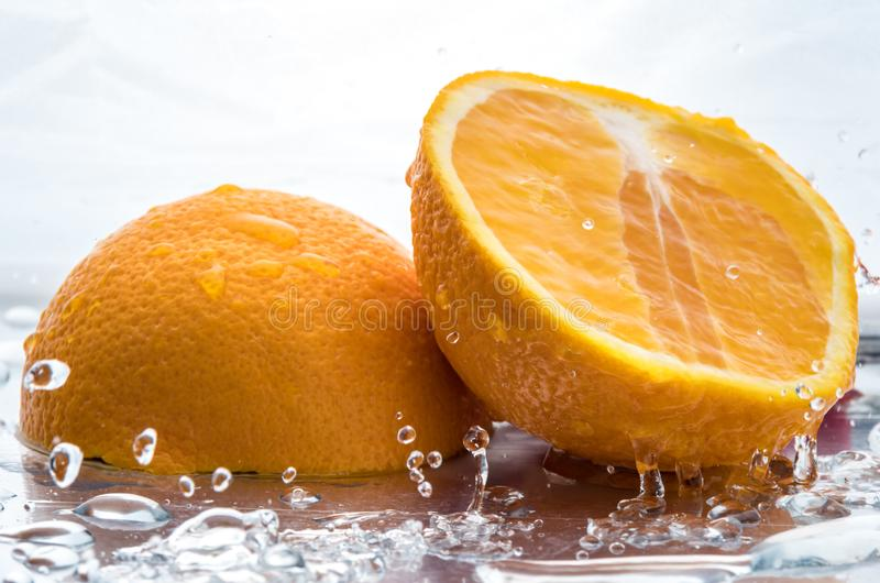 Two halves of juicy orange close up with a splash of water on them and flying water above.  stock photo