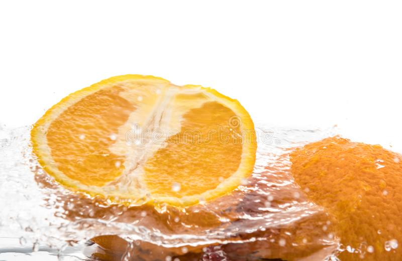 Two halves of juicy orange close up with a splash of water on them and flying water above.  royalty free stock images