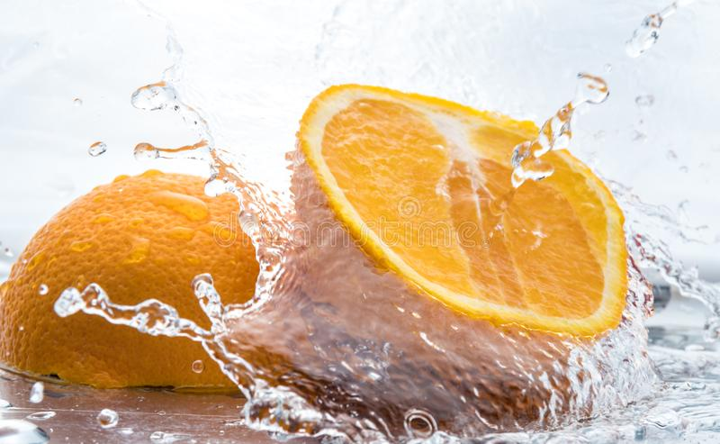 Two halves of juicy orange close up with a splash of water on them and flying water above.  royalty free stock image