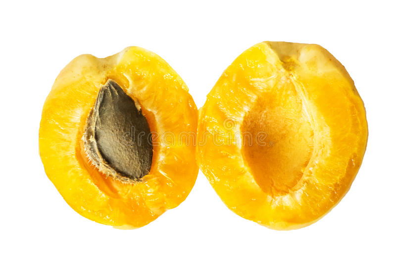 Two halves of a juicy ripe pineapple apricot with a bone inside. Isolated halved fruit on a white background. Top view. royalty free stock photo