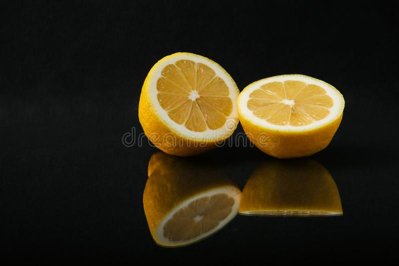 Two halves of lemon on a black background close up with reflection. Citrus fruit isolated  on black background royalty free stock photos