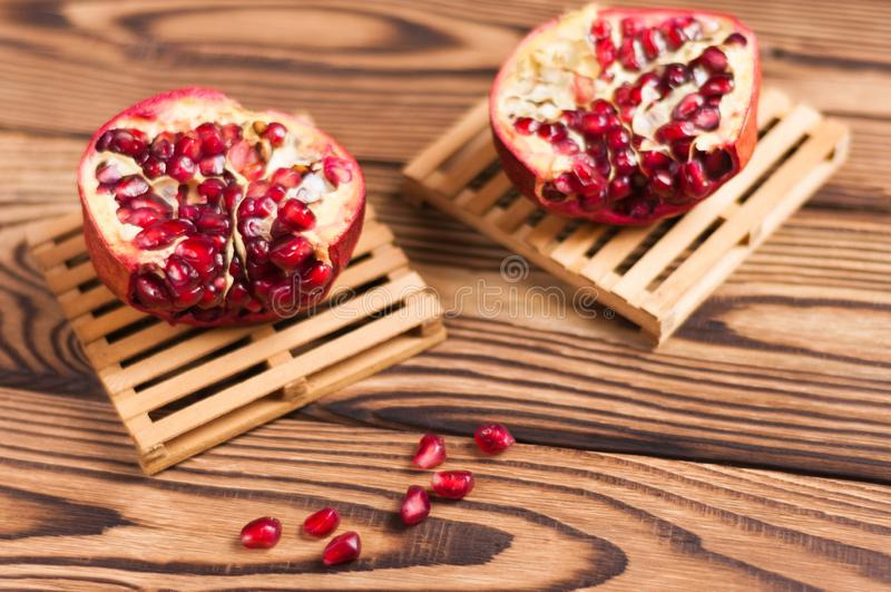 Two halves of red ripe fresh pomegranate on wooden pallets on old brown weathered rustic planks royalty free stock images