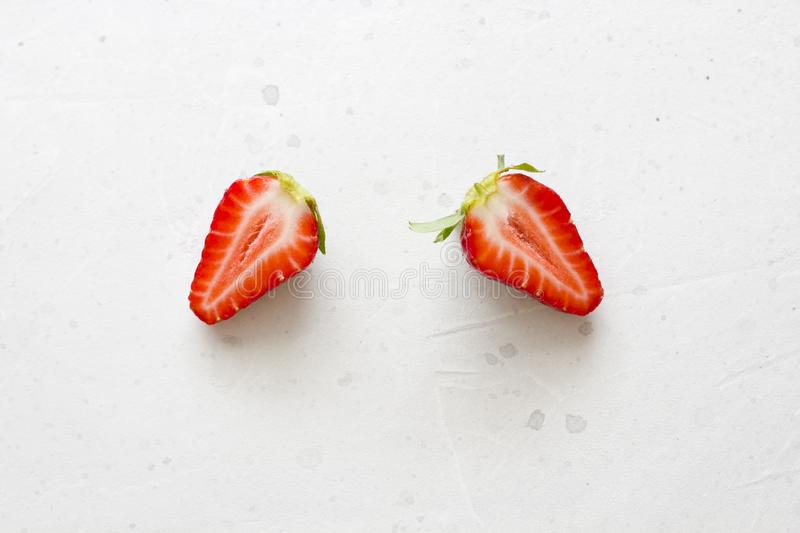 Two halves of strawberries. Cut red beautiful strawberries on a light white concrete background. Flat Lay, Top View, Copy Space. For Your Text stock photography