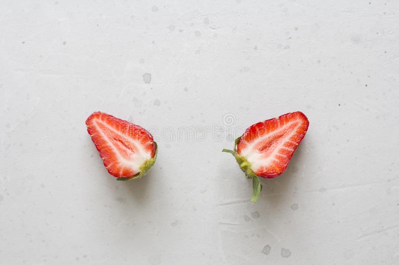 Two halves of strawberries. Cut red beautiful strawberries on a light white concrete background. Flat Lay, Top View, Copy Space. For Your Text royalty free stock photos