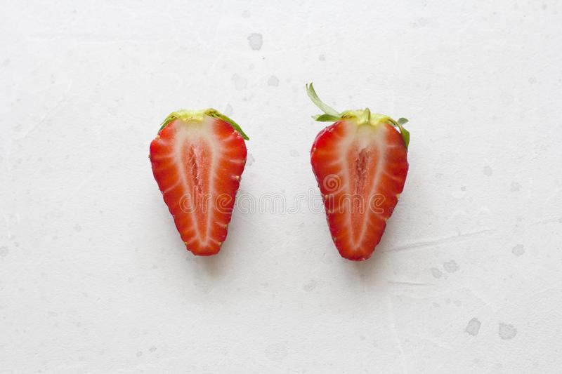 Two halves of strawberries. Cut red beautiful strawberries on a light white concrete background. Flat Lay, Top View, Copy Space. For Your Text royalty free stock photography