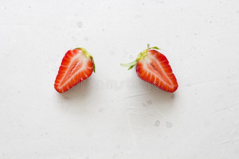 Two halves of strawberries. Cut red beautiful strawberries on a light white concrete background. Flat Lay, Top View, Copy Space. For Your Text stock photo