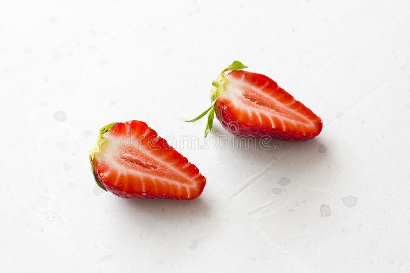 Two halves of strawberries. Cut red beautiful strawberries on a light white concrete background. Top View, Copy Space For Your. Text stock photo