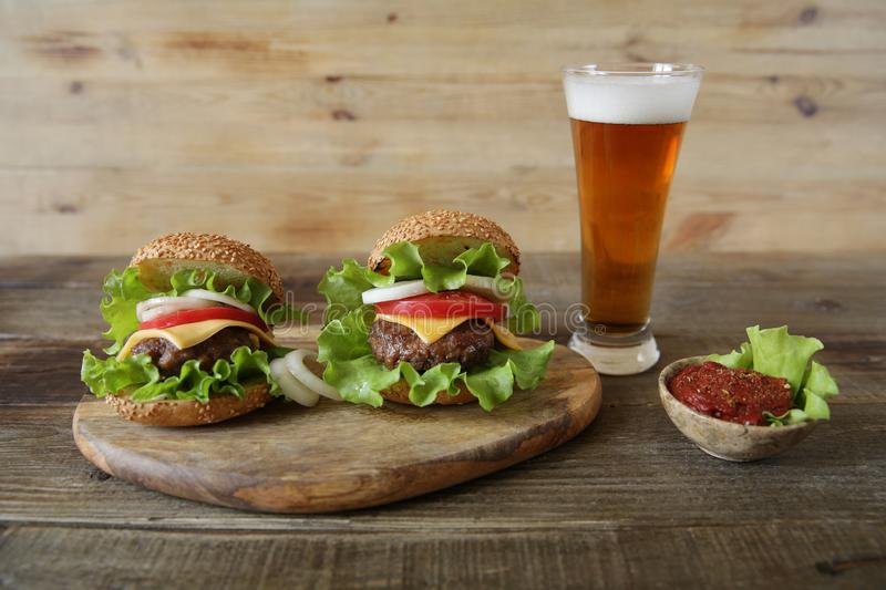 Two hamburger with beef patty, with cheese, pickles, tomatoes, onions, lettuce and tomato sauce in a saucer with a glass of beer o stock image