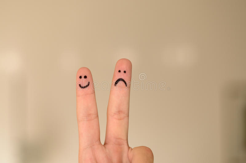 Two hand drawn emoticon faces on a persons fingers. One happy and smiling and the other unhappy, sad or depressed isolated on a neutral background with copy stock images