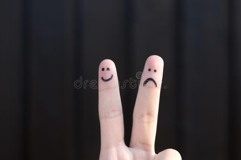 Two hand drawn emoticon faces on a persons fingers. One happy and smiling and the other unhappy, sad or depressed over a black background with copy space royalty free stock image