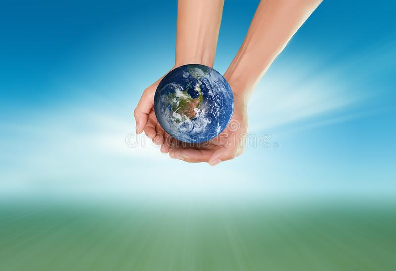 Save environment concept. Two hand holding the earth on blurred sea landscape background, Save earth save environment concept, Elements of this image furnished royalty free stock photography