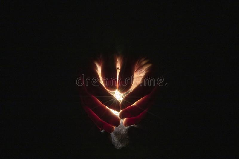 Two hand holding a light bulb in the dark background stock photo