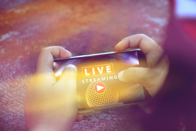 Two hand holding smart phone with Live Streaming concert. Live streaming word and microphone on screen mobile phone, music online concept royalty free stock photo