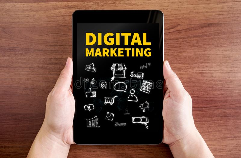 Two hand holding tablet with Digital marketing and doodle icon o. N screen at dark brown table top,Digital business concept royalty free stock photography