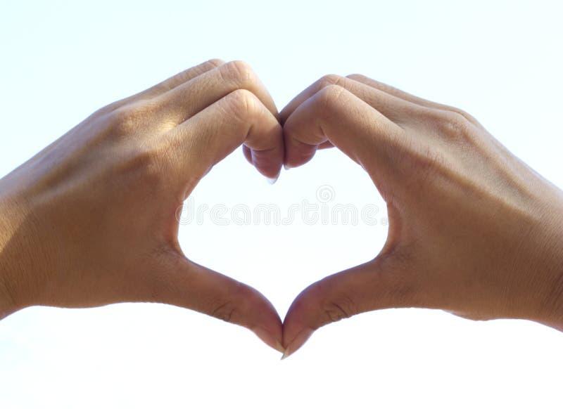 Two hand make heart on sky stock photos