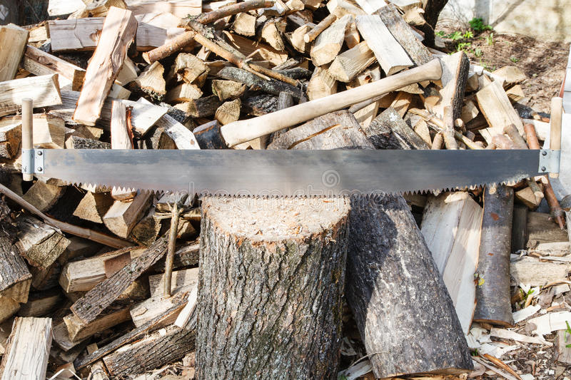 Two-handled saw and ax in chopping block. Pile of firewood on rustic courtyard stock photography