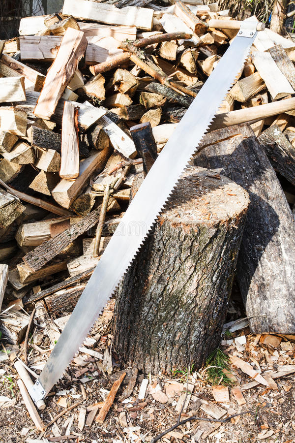 Two-handled saw and ax in chopping deck. Two-handled saw and ax in deck for chopping firewood, pile of wood on rustic courtyard stock image
