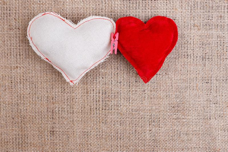 Two handmade fabric hearts clipped with clothespin on sackcloth, royalty free stock photography