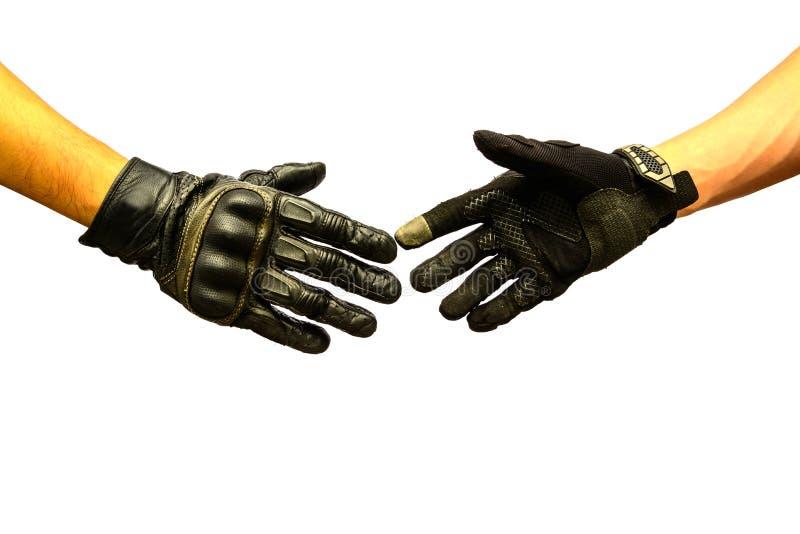 Two hands biker meet in hand shake. Two hands biker gloves meet in hand shake royalty free stock photography