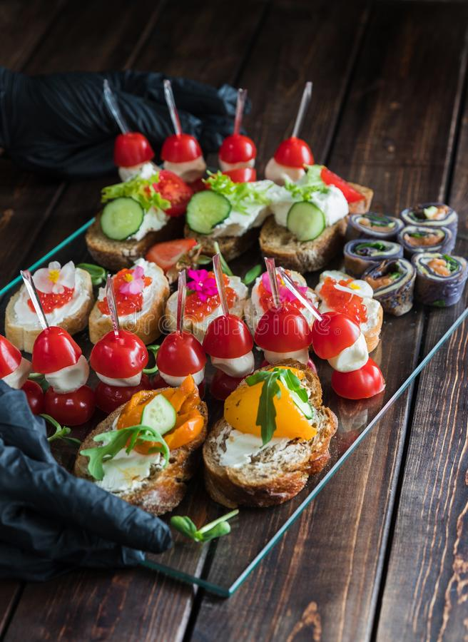 Two hands in black gloves holding a snack tray on woody background: rolls, canapes, rolls, stuffed tomatoes, sandwich with caviar stock photography
