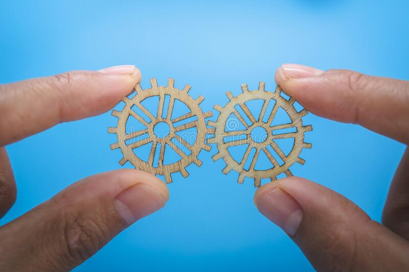 Two hands of businessmen collect gear from the gears of the details of puzzles.  The concept of a business idea. Teamwork. stock image