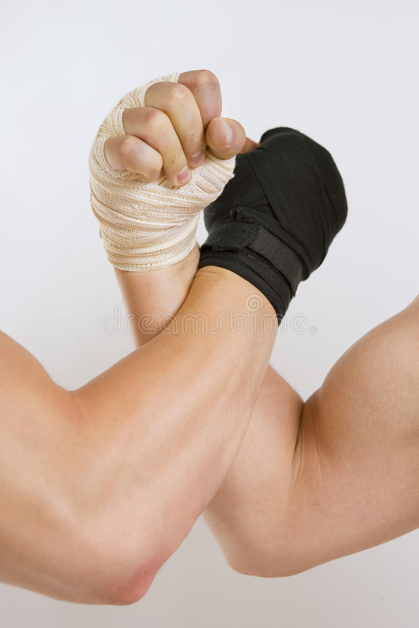 Two hands clasped arm wrestling, the struggle of black and white. Hand in a white glove and hand in a black glove clasped arm wrestling, good and evil opposition stock photos