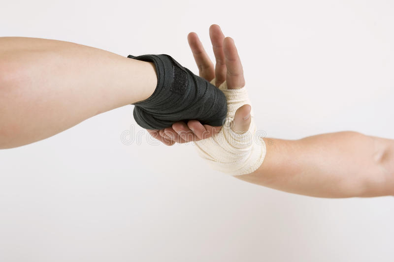 Two hands clasped arm wrestling, the struggle of black and white. Hand in a white glove and hand in a black glove clasped arm wrestling, good and evil opposition royalty free stock image