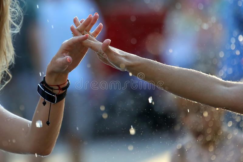 Two hands in the drops of water join together. The two hands in the drops of water join together royalty free stock photos