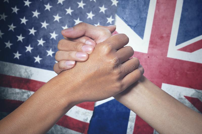 Two hands with England and United States flag. Concept of peace. Two hands of people posing partnership with England and United States flag in the background stock images