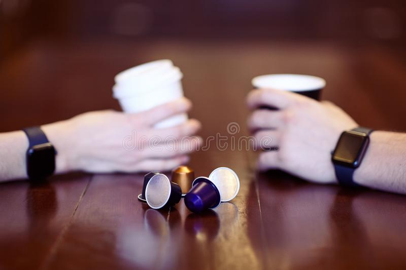 Two hands with equal black electronic wrist watches, holding cups of coffee, white and black, on the wooden table with some replac royalty free stock image