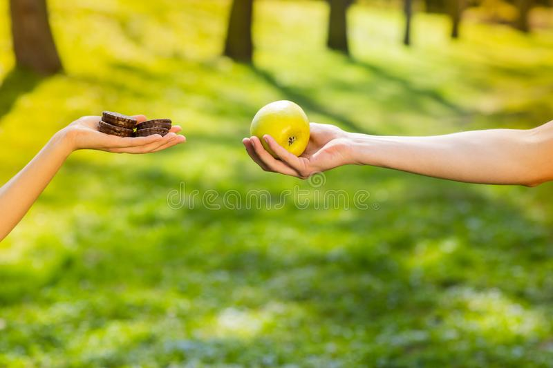 Two hands, female and male, holding and comparing cookie and apple. Background of the green park stock images