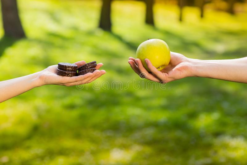 Two hands, female and male, holding and comparing cookie and apple. Background of the green park stock photo