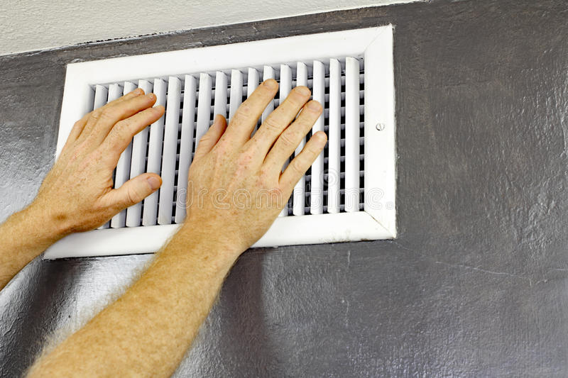 Two Hands in Front of an Air Vent. A pair of adult male hands feeling the flow of air coming out of an air vent on a wall near a ceiling. Man with hands in front royalty free stock images
