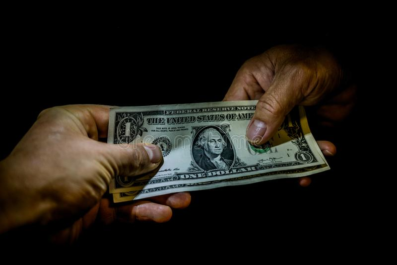 Two hands handing over american dollar banknotes to each other. Concept of tourist business profit, foreign investment, paying for the goods, shopping, money stock photography