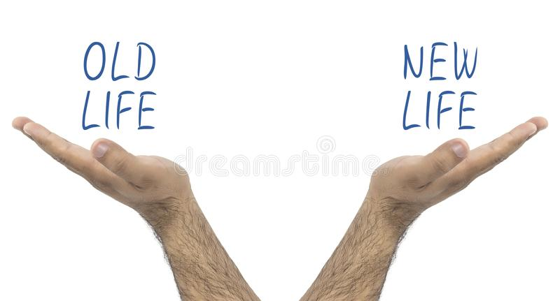 Two hands holding in balance old life and new life.  royalty free stock photography