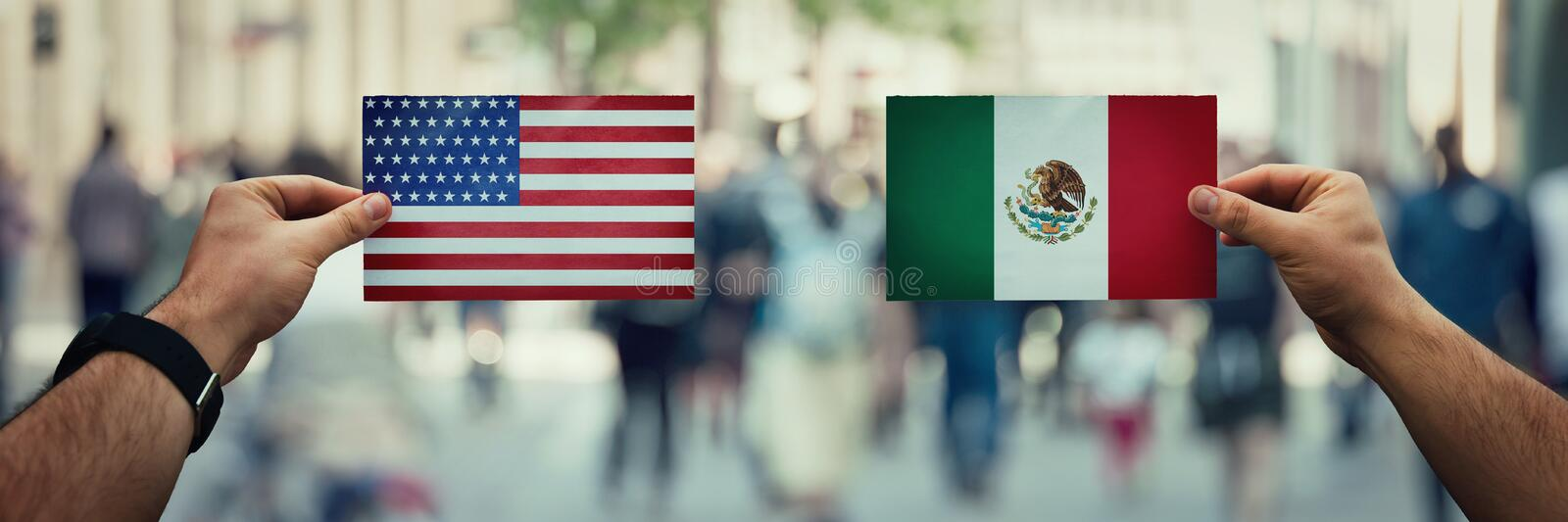 Usa vs mexico. Two hands holding different flags, Mexico vs United States on politics arena over crowded street background. Future strategy, relations between royalty free stock photos