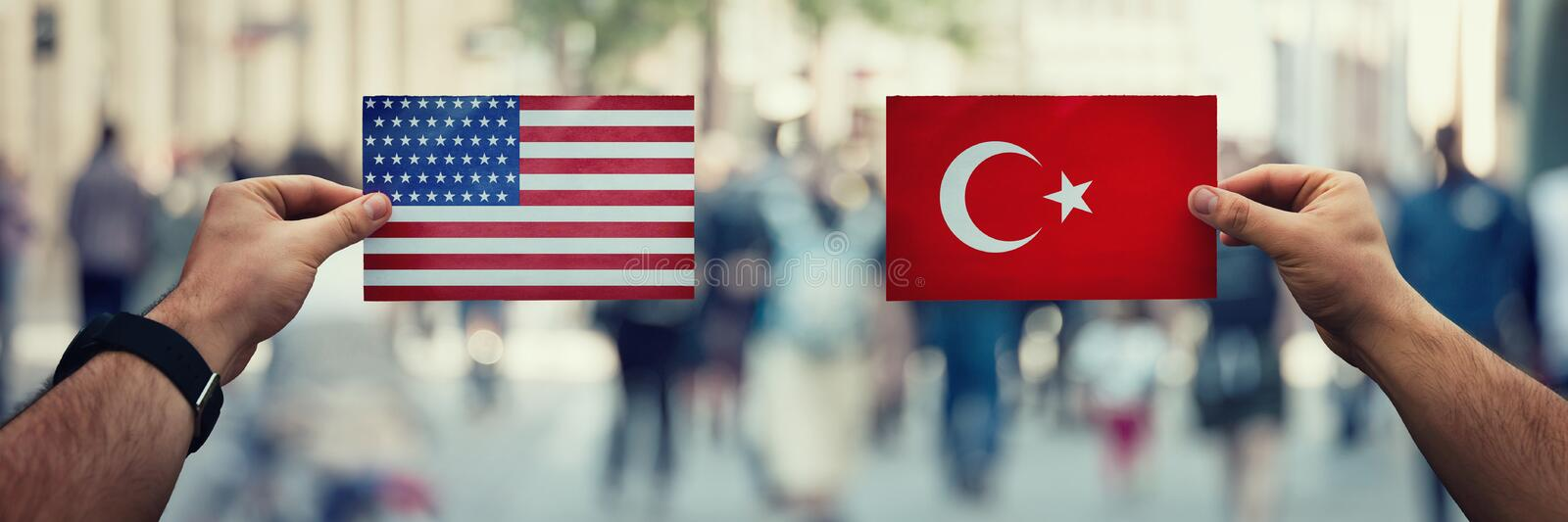 Two hands holding different flags, US vs Turkey on politics arena over crowded street background. Diplomacy future strategy,. Relations between countries royalty free stock photos