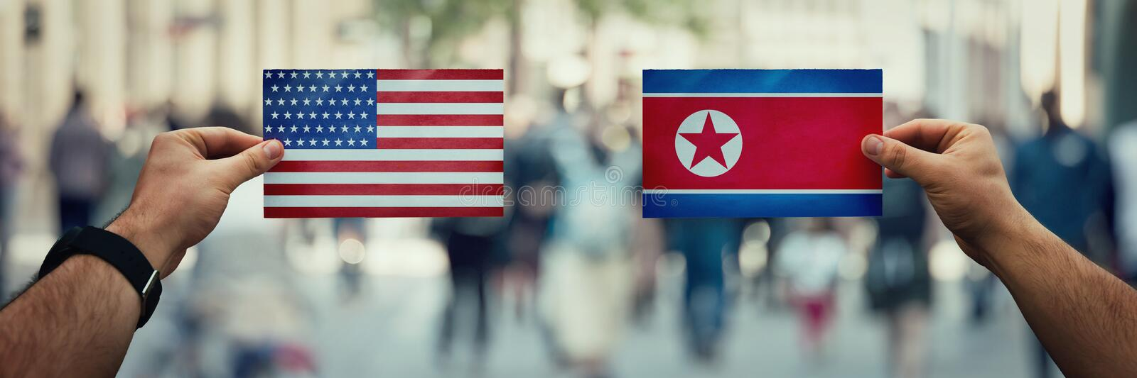 Usa vs korea. Two hands holding different flags, USA vs North Korea Republic on politics arena over crowded street background. Future strategy, relations between stock images