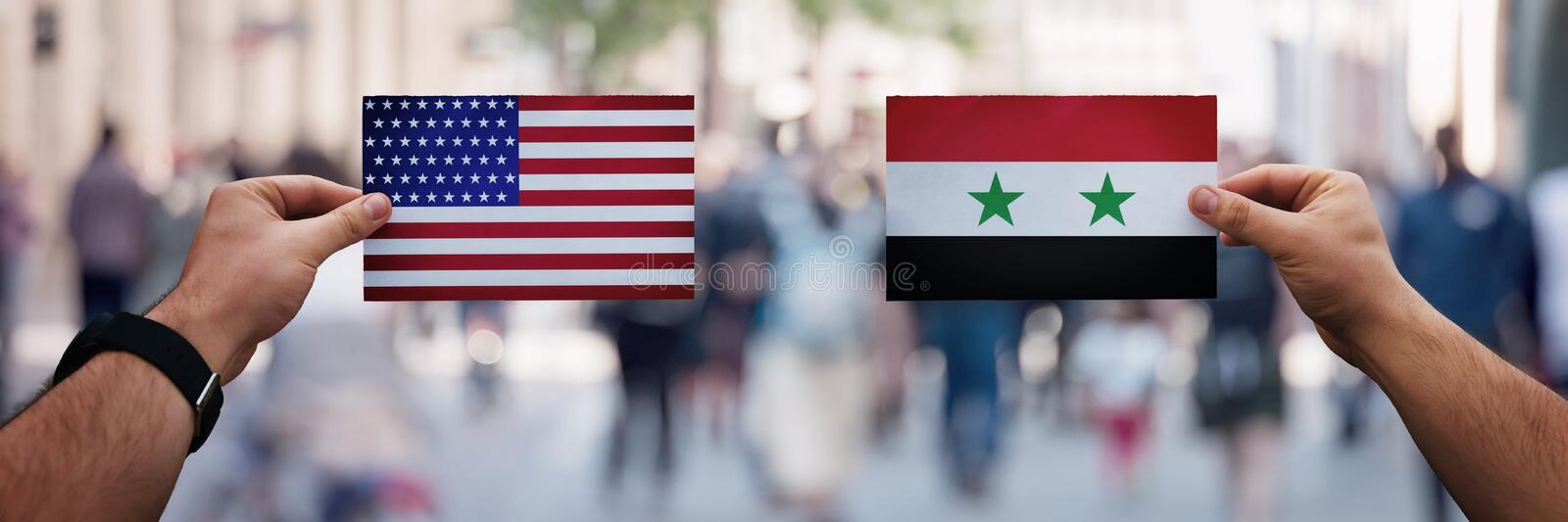 Two hands holding different flags, USA vs Syria on politics arena, relations between countries. Cooperation or opposite conflict royalty free stock photo