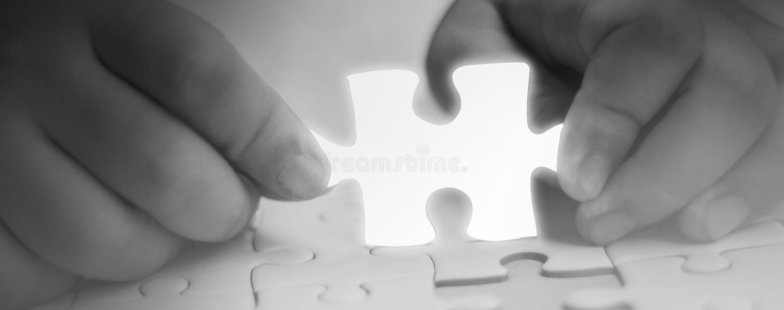 Two hands holding jigsaw puzzle piece glowing white glow piece missing components,Abstract concept business with success,goals and stock images