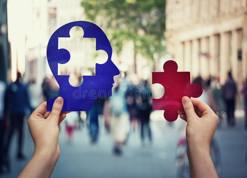 Two hands holding a paper with human head and a puzzle piece. Finding a cure to heal the disease. Mental health concept, memory. Loss and dementia disease royalty free stock photo
