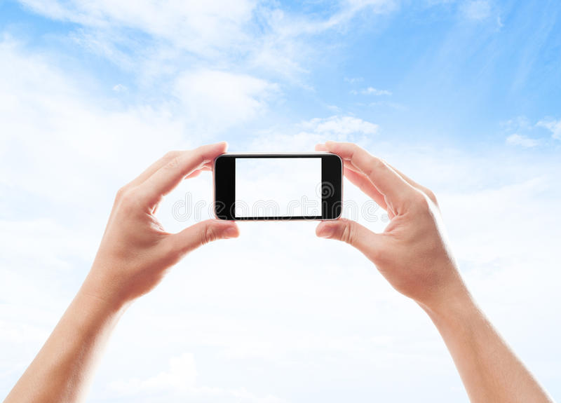 Two hands holding smart phone. On the background of blue sky with clouds stock photography