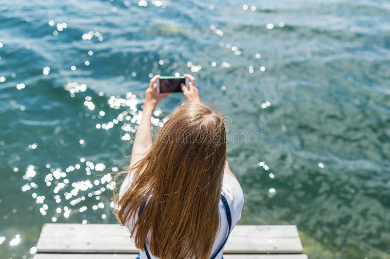 Two hands holding smart phone on water background.  stock images
