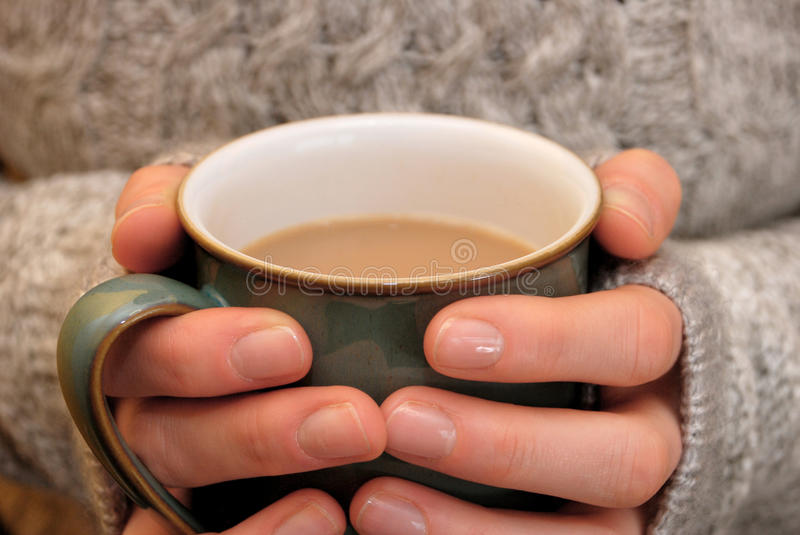 Two hands keeping warm, holding a hot cup of tea or coffee. Against a cozy sweater stock photos
