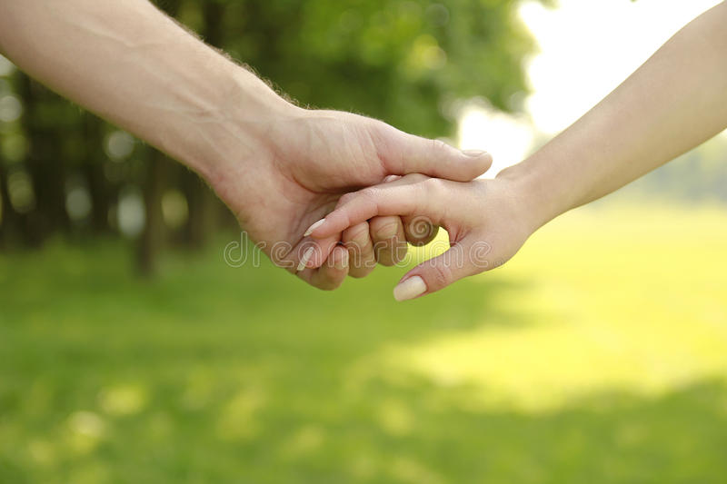 Two hands of a loving couple on nature royalty free stock images