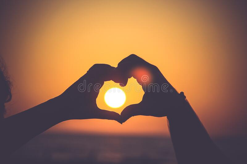Two Hands Making a Heart with Sunset in Background stock photography